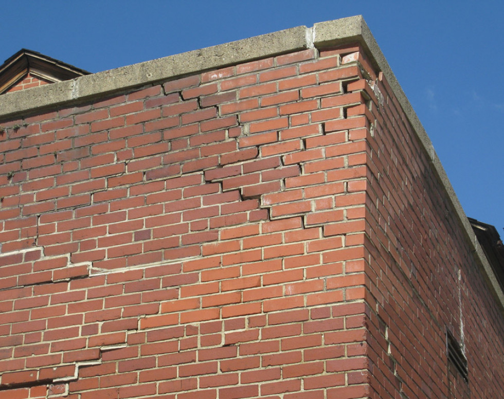 Structural brick wall movement requires demolition and rebuilding. Note the different color brick that indicates failed attempts at past repairs.