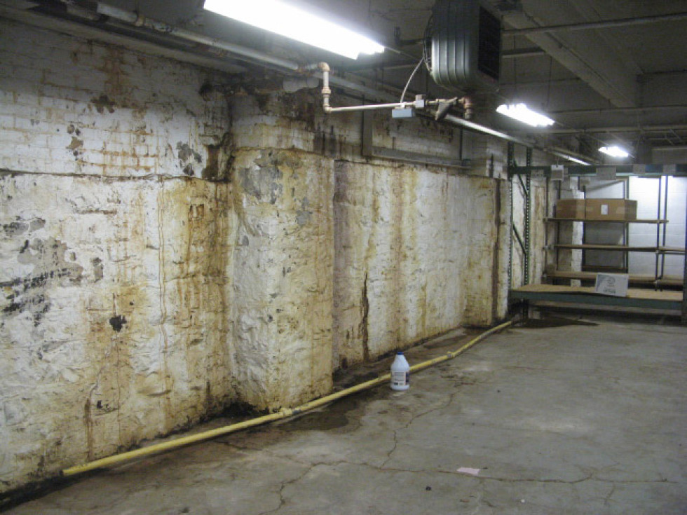 Long term water penetration through a warehouse foundation wall will affect the use of the building space and need expensive dewatering repairs.